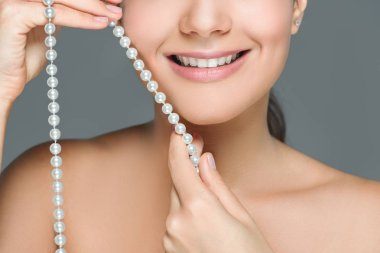 cropped shot of smiling woman with white teeth and pearls in hands isolated on grey