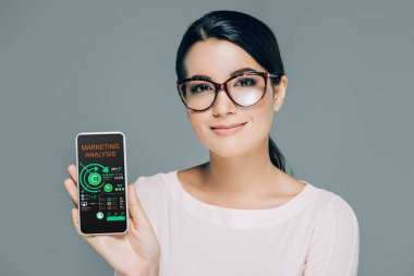 portrait of smiling woman in eyeglasses showing smartphone with marketing analysis on screen isolated on grey