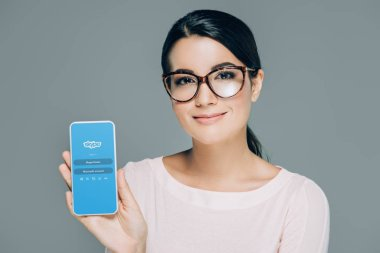 portrait of smiling woman in eyeglasses showing smartphone with skype app on screen isolated on grey