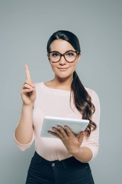 portrait of smiling brunette woman in eyeglasses with digital tablet pointing up isolated on grey