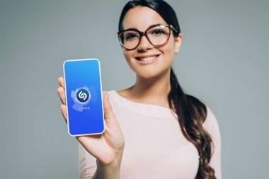 smiling girl showing smartphone with shazam app, isolated on grey