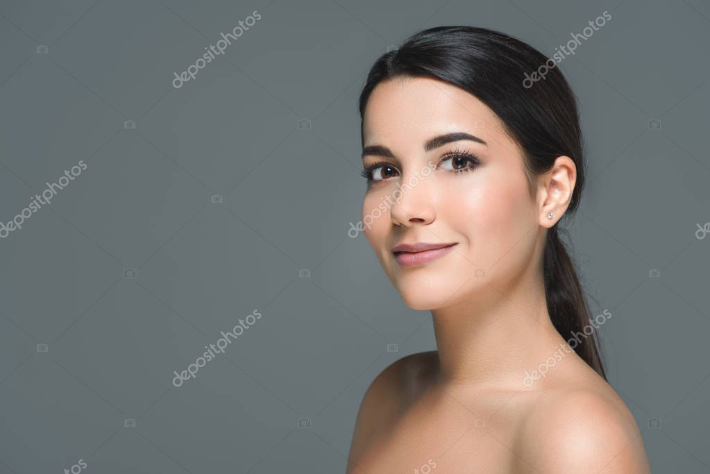 portrait of brunette smiling woman looking at camera isolated on grey