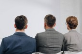 Fotografie rear view of three businessmen sitting on chairs during training in hub