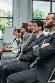 side view of businesspeople sitting on chairs during training in hub