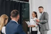 obchodní trenéry stojící na pódiu s dokumenty v náboji