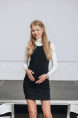 Fotografie pregnant businesswoman touching belly and looking at camera in hub