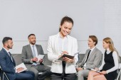 Fotografie Business-Coach, etwas zu schreiben, zu Notebook vor Geschäftsleute beim Training im hub