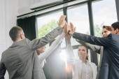 businesspeople giving high five after training in hub