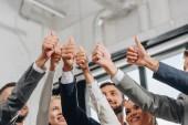Niedrigwinkel-Ansicht lächelnder Geschäftsleute, die Daumen hoch in der Nabe zeigen