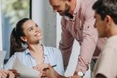Üzletasszony és üzletember néztek egymásra ülésen irodában mosolyogva