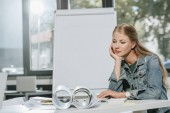 tired beautiful businesswoman resting chin on hand at table in office