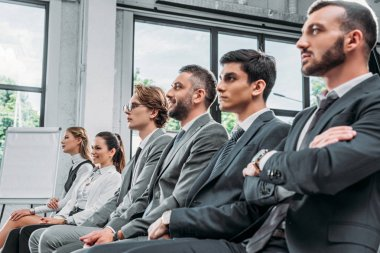 businesspeople sitting on chairs during training in hub and looking away