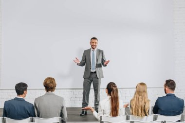 handsome business coach standing on stage and gesturing during training in hub