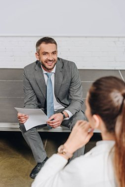 smiling businessman sitting on stage in hub and looking at businesswoman