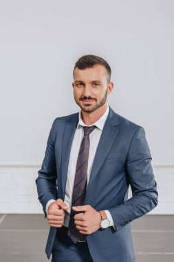 handsome businessman touching jacket and looking at camera in hub