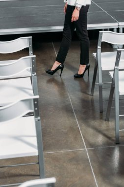 cropped image of businesswoman walking between stage and chairs in hub