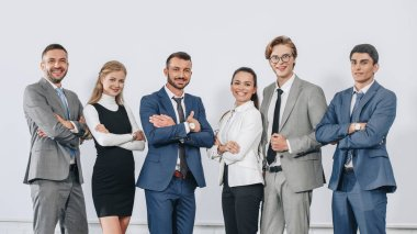 smiling businesspeople with crossed arms posing near board after training in hub and looking at camera