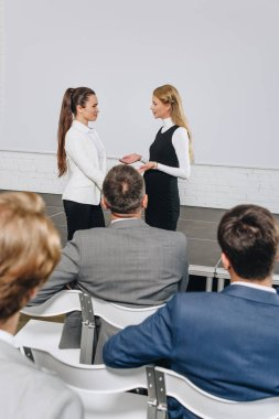 attractive business coach and businesswoman talking at training in hub