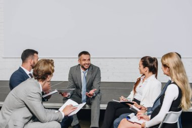 handsome business coach looking at businesspeople during training in hub