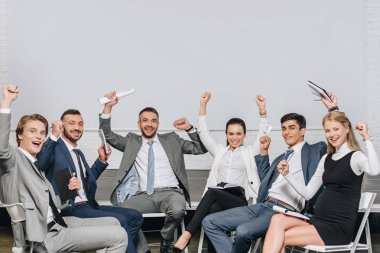 happy businesspeople with raised hands sitting on chairs at training in hub