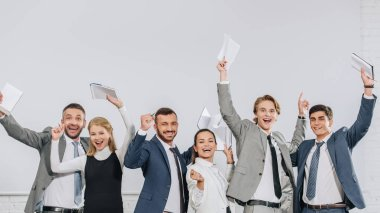 happy businesspeople standing with raised hands and holding notebooks in hub