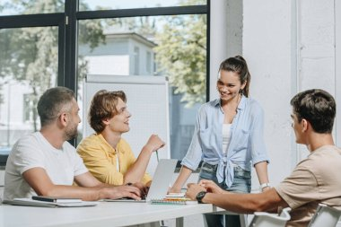 businessmen sitting at table during meeting and looking at businesswoman in office