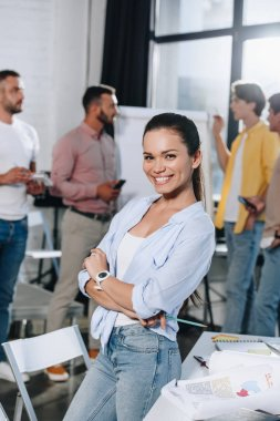 smiling businesswoman with crossed arms looking at camera during meeting in office