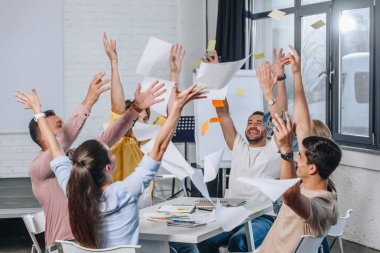 happy businesspeople throwing up documents during meeting in office