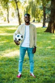 smiling handsome african american man standing with football ball in park