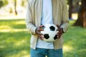 Fotografie oříznutý obraz afroamerické muže drží fotbalový míč v rukou v parku