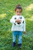 Fotografie entzückende afroamerikanische Kind hält Fußball-Ball und wegschauen im park
