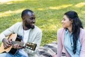 smiling handsome african american boyfriend playing acoustic guitar for girlfriend in park