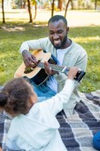 Fotografia afro-americana figlia toccare la chitarra mentre suo padre che giocano nel parco