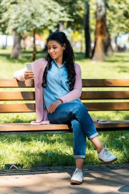 Cheerful beautiful african american woman looking at smartphone on wooden bench in park stock vector
