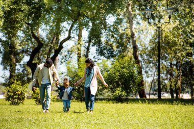african american parents and daughter holding hands and walking on green grass in park
