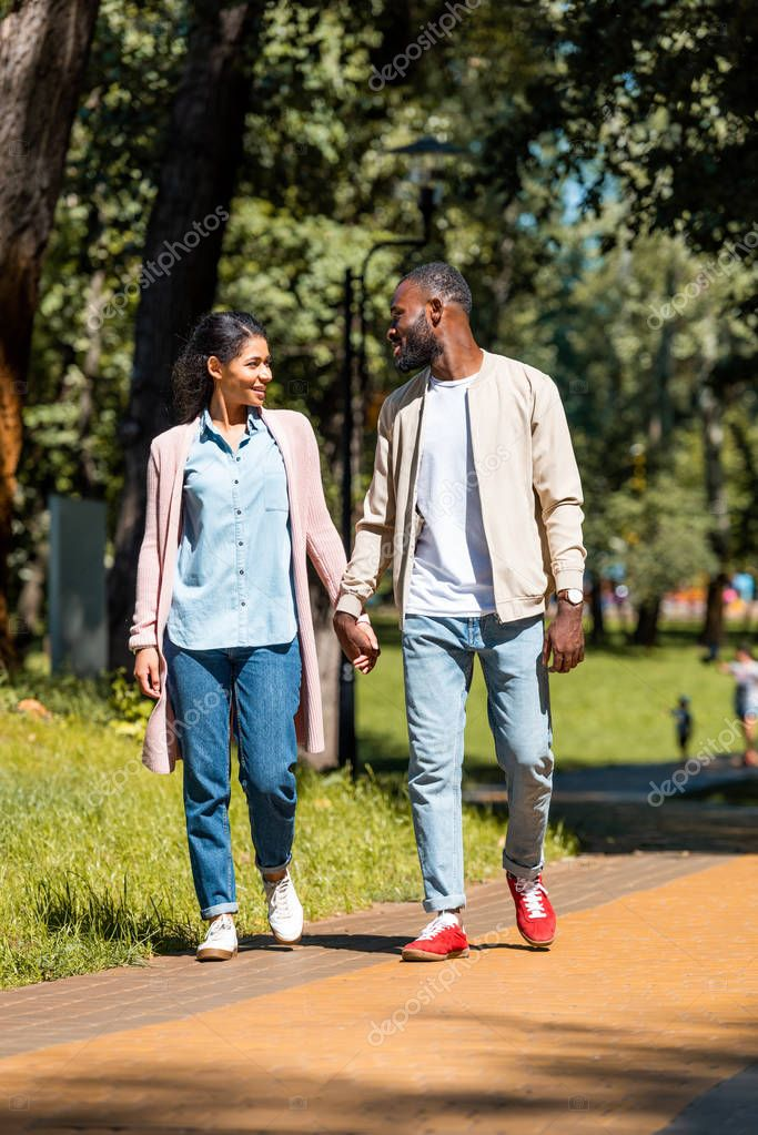 smiling african american couple holding hands and walking in park