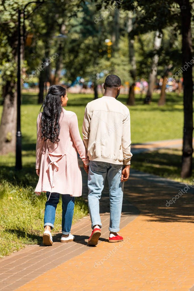 rear view of african american couple holding hands and walking in park