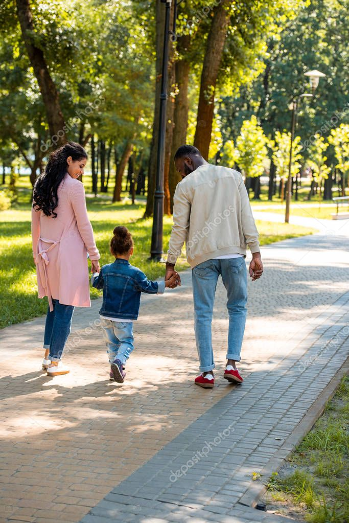 back view of african american parents and daughter holding hands and walking in park