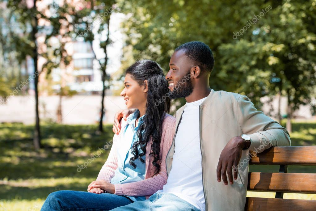smiling african american couple sitting on wooden bench in park and looking away