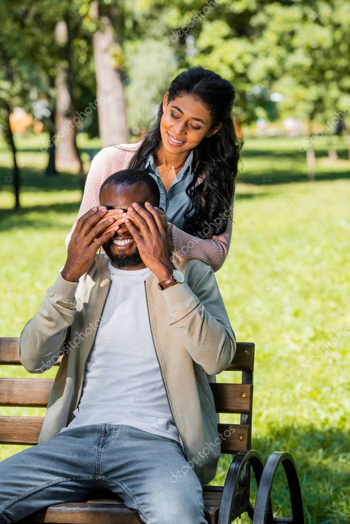 african american girlfriend closing boyfriend eyes while he sitting on bench in park