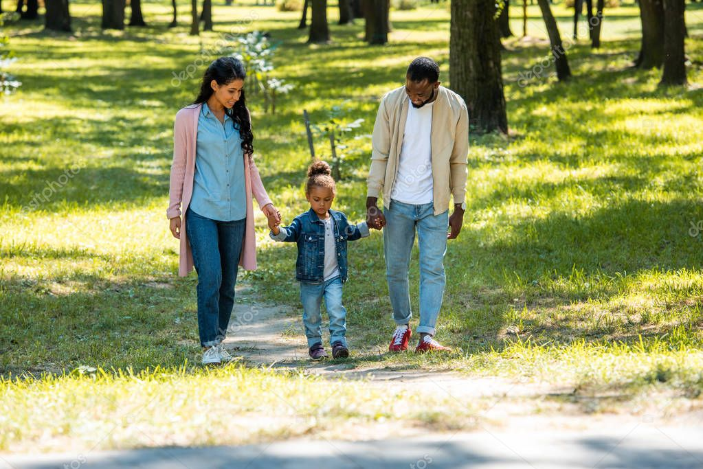 african american parents and daughter holding hands and walking in park