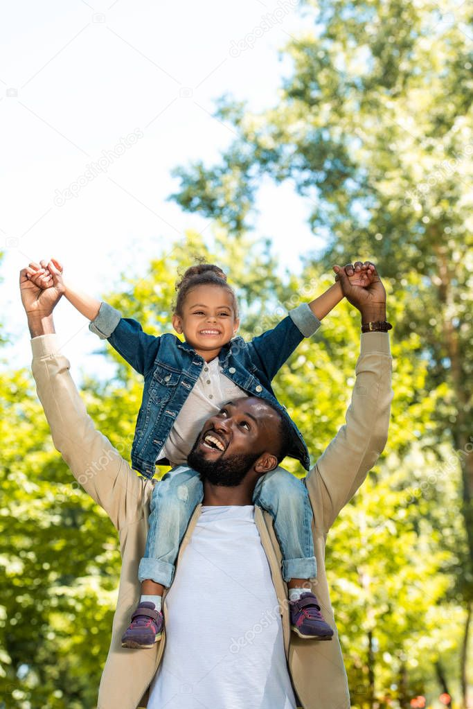 happy african american father holding daughter on shoulders in park