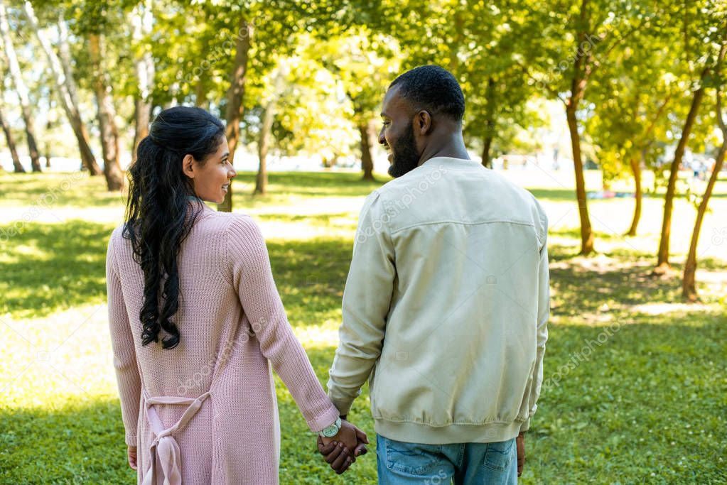 african american couple holding hands and looking at each other in park
