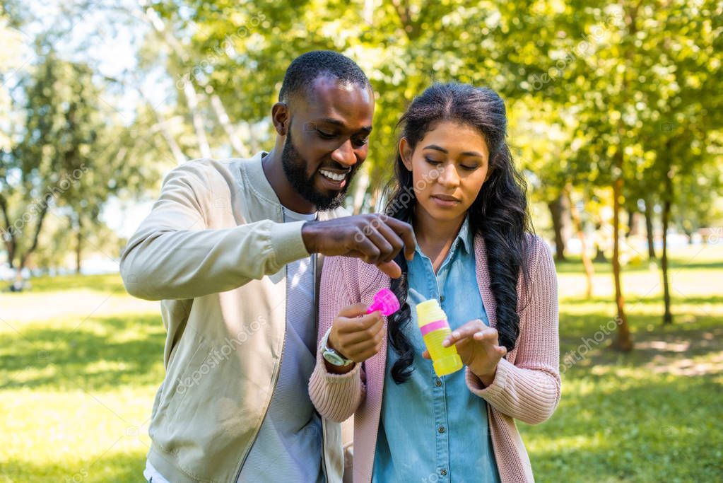 african american couple having fun with bottle for soap bubbles in park