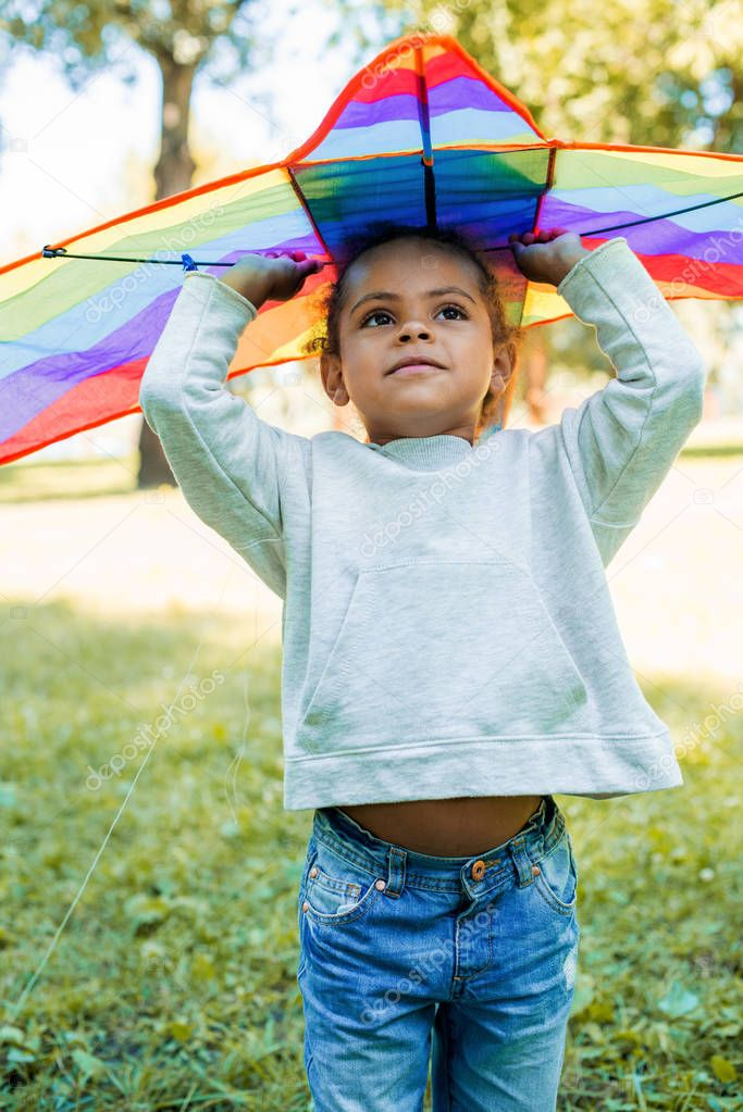 adorable african american kid holding rainbow kite above head in park