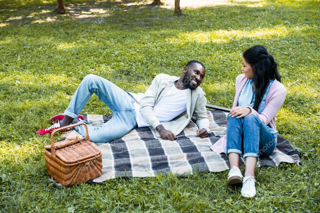 african american couple looking at each other at picnic in park
