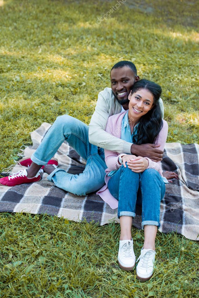 high angle view of smiling african american boyfriend hugging girlfriend in park