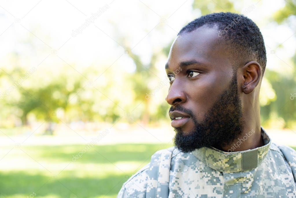 portrait of african american soldier in military uniform looking away in park