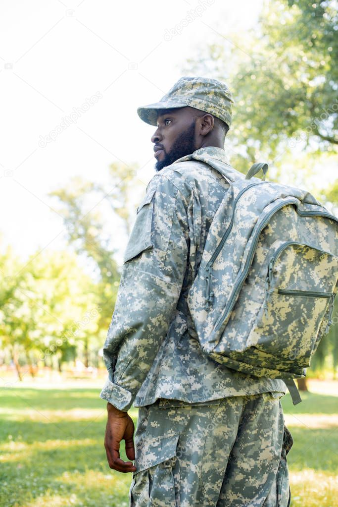 low angle view of african american soldier in military uniform and bag looking away in park