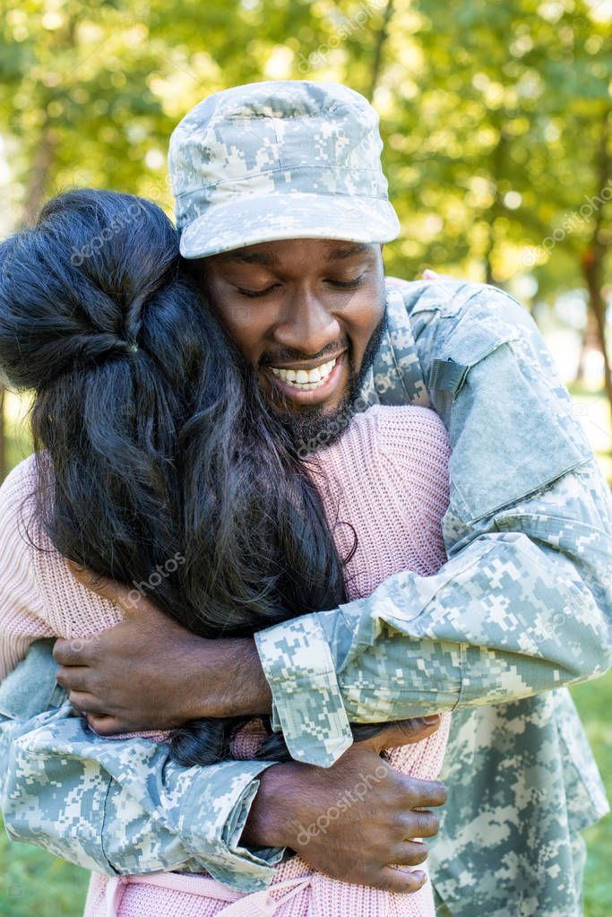 smiling african american soldier in military uniform cuddling girlfriend in park